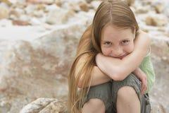 逗人喜爱的青春期前的女孩坐岩石 免版税库存图片