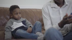 逗人喜爱的非裔美国人的使用与玩具的妇女和她的小逗人喜爱的儿子坐长沙发在舒适客厅 影视素材