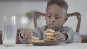 逗人喜爱的非裔美国人的儿童男孩画象有肮脏的嘴唇的在做曲奇饼金字塔的牛奶以后参加由桌  股票录像