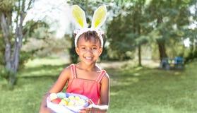 逗人喜爱的非裔美国人的女孩佩带的兔宝宝耳朵,拿着复活节ba 免版税库存图片
