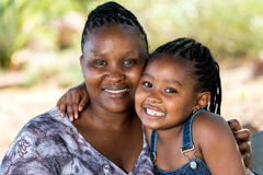 逗人喜爱的非洲拥抱母亲和的孩子户外 免版税库存照片