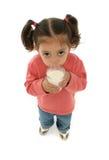 逗人喜爱的饮用的女孩少许牛奶 免版税图库摄影