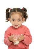 逗人喜爱的饮用的女孩少许牛奶 库存照片