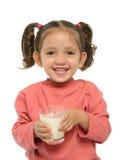 逗人喜爱的饮用的女孩少许牛奶 图库摄影