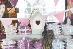逗人喜爱的鸟议院、微型枕头和淡紫色花束在架子 免版税库存照片