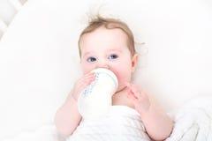 逗人喜爱的从一个瓶的婴孩饮用奶在一个白色小儿床 库存图片