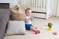 逗人喜爱的10个月使用与在地板上的玩具的小孩男孩 免版税库存图片