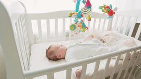 逗人喜爱的3个月在小儿床和看玩具转盘的男婴 股票视频
