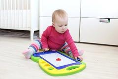 逗人喜爱的10个月女婴演奏磁性儿童的绘图板 库存图片
