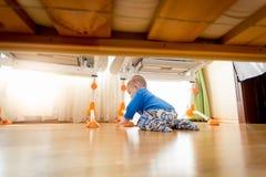 逗人喜爱的9个月爬行在床下的男婴 免版税库存图片