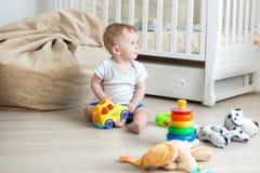 逗人喜爱的10个月男婴获得与玩具的乐趣在卧室 库存照片