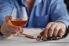逗人喜爱的年轻人喝威士忌酒在桌上 库存图片