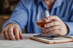 逗人喜爱的年轻人喝威士忌酒在桌上 免版税库存图片