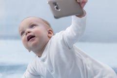 逗人喜爱的婴儿男孩做与手机的selfie 拍与智能手机的可爱的微笑的小孩孩子一张selfie照片 库存图片