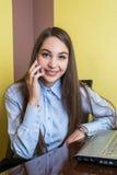 逗人喜爱的年轻女实业家微笑和谈话在电话在办公室 免版税库存照片