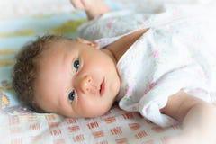 逗人喜爱的婴孩在床上说谎 免版税库存图片