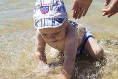 逗人喜爱的婴孩在海,他的父亲insur的手飞溅 库存图片