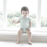 逗人喜爱的婴孩在绝尘室在窗口附近在家坐 美丽的婴孩可能是男孩或女孩和穿着身体衣服 库存图片