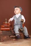 逗人喜爱的婴孩坐手提箱,拿着葡萄酒电话 免版税图库摄影