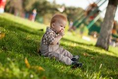 逗人喜爱的婴孩坐草 免版税库存图片