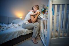 逗人喜爱的婴孩得到在晚上惊吓了在拥抱年轻有同情心的母亲 免版税库存图片
