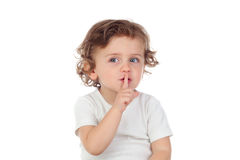 逗人喜爱的婴孩投入了食指到嘴唇作为沈默的标志 免版税库存图片