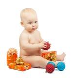 逗人喜爱的婴孩拿着红色球,圣诞节礼物盒 免版税库存照片