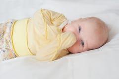 逗人喜爱的婴孩明亮的画象有手指的在嘴在白色床上 库存图片