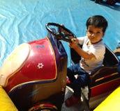 逗人喜爱的婴孩骑马哄骗汽车 免版税库存图片
