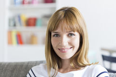 逗人喜爱的30岁的妇女画象白色现代公寓的 库存照片