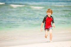 逗人喜爱的7岁红色rushwest游泳衣enjoing的夏时的男孩在与白色沙子和绿色海洋的热带海滩 免版税库存照片
