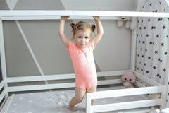 逗人喜爱的2年小女孩在她的白色床上在家 免版税库存照片