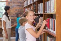 逗人喜爱的寻找书的学生和老师在图书馆里 免版税库存图片