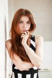 逗人喜爱的年轻摆在黑白色的墙壁附近的红头发人时髦的妇女画象镶边了拥抱的礼服接触她的下巴 免版税库存图片