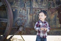 逗人喜爱的年轻混合的族种男孩获得乐趣在古色古香的机械附近 免版税库存照片