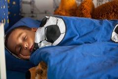 逗人喜爱的年轻男孩与taddy睡觉在他的床上 免版税库存照片