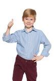 逗人喜爱的年轻男孩举行他的赞许 免版税库存图片