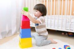 逗人喜爱的2年男孩在家演奏教育玩具 免版税库存照片