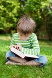 逗人喜爱的年轻男孩坐草和读 免版税库存照片