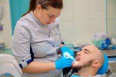 逗人喜爱的年轻男孩检查他的牙在一个牙齿办公室在医生 免版税库存照片