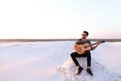 逗人喜爱的年轻男性阿拉伯人享受吉他的声音,坐小山  库存图片
