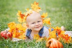 逗人喜爱的滑稽的可爱的白肤金发的白种人男婴特写镜头画象有蓝眼睛的在说谎在草地的T恤杉和牛仔裤连裤外衣 库存照片