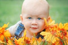 逗人喜爱的滑稽的可爱的白肤金发的白种人男婴特写镜头画象有蓝眼睛的在说谎在草地的T恤杉和牛仔裤连裤外衣 图库摄影