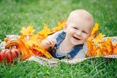 逗人喜爱的滑稽的可爱的白肤金发的白种人男婴画象有蓝眼睛的在说谎在草地草甸的T恤杉和牛仔裤连裤外衣 免版税库存照片