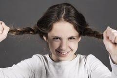 逗人喜爱的滑稽的女孩撕毁她的有巨大的微笑的头发 库存照片