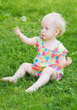 逗人喜爱的滑稽的女婴坐与花的草 库存照片
