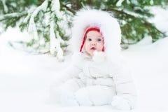 逗人喜爱的滑稽的矮小的婴孩在冬天公园在大树下 免版税库存照片