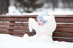 逗人喜爱的滑稽的婴孩坐一条长凳在公园 免版税库存照片