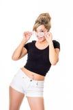 逗人喜爱的年轻金发碧眼的女人画象,白色短裤和黑暗的上面的与 免版税图库摄影