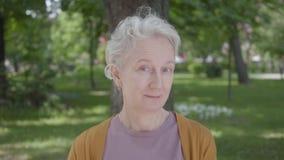 逗人喜爱的smilling的老妇人画象有灰色坐在绿色惊人的公园的头发和蓝眼睛的 可爱成熟 影视素材